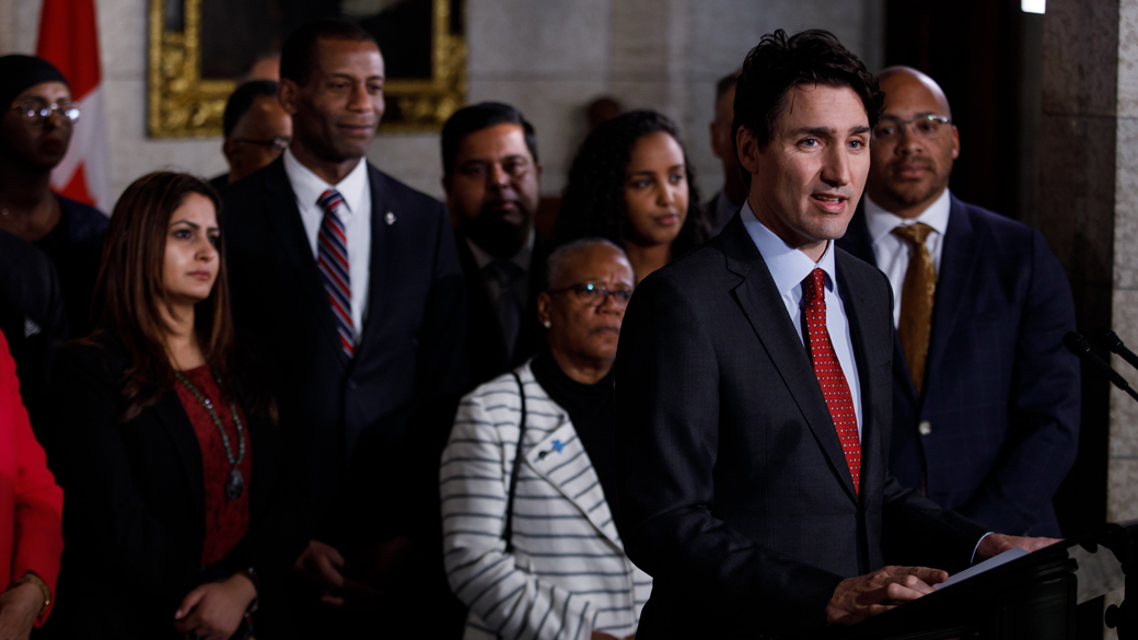 Inside Parliament, community leaders and members of parliament stand behind Prime Minister Trudeau while he makes an announcement