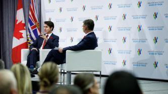PM Trudeau addresses the audience while the moderator listens