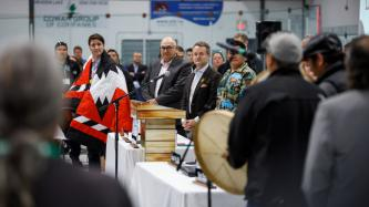 PM Trudeau wears a ceremonial blanket and listens