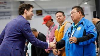 PM Trudeau shakes hands with a man