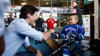 PM Trudeau shakes hands with a young boy in hockey equipment
