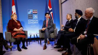 PM Justin Trudeau sits laughing with the PM of Norway, Ema Solberg