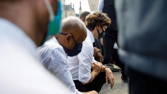 PM Trudeau and Minister Hussen kneel in a crowd