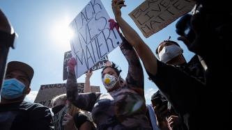 Protesters hold signs up in a crowd