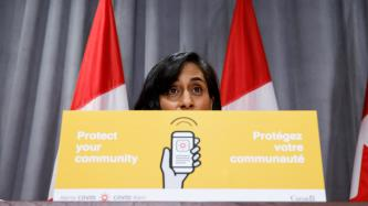 Minister Anand behind a COVID Alert podium card