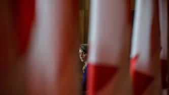A view of Minister Joly, behind the Canadian flags