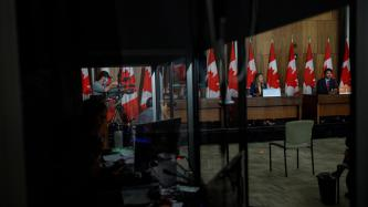 A view of PM Trudeau and Minister Joly from a window