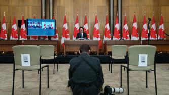 Photographer at work in front of PM Trudeau, DPM Freeland and Minister Blair are on a screen