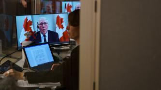 Woman at work with a tablet with Minister Bill Blair on a screen