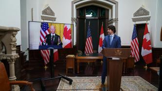 PM Trudeau stands at a podium looking at a screen of President Biden at a podium