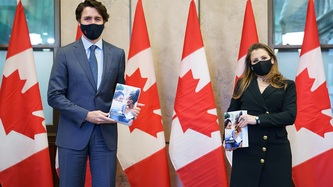 PM Trudeau and DPM Freeland stand holding a book, a row of Canadian flags behind them