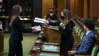 Deputy Prime Minister Chrystia Freeland hands books over to someone as Prime Minister Trudeau looks on