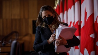 Deputy Prime Minister Chrystia Freeland holds papers and walks near a row of Canadian flags